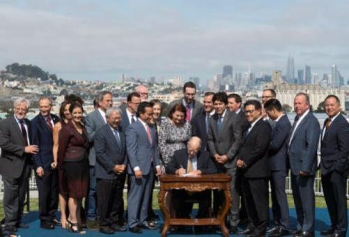 布朗(中)签署提案计划。(州长办公室提供)