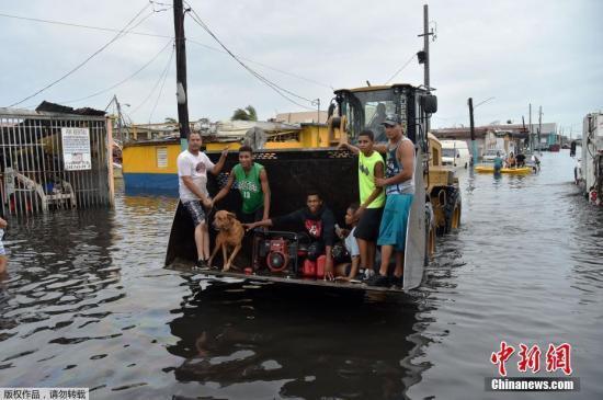 9月21日,波多黎各遭遭飓风侵袭,当地民众乘坐挖掘机渡过积水的街道。