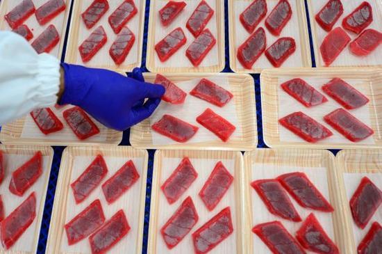 资料图片:在山东省荣成市蓝润金枪鱼加工基地,工人将金枪鱼生鱼片装盘。新华社记者 郭绪雷 摄