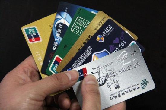 资料图片:山东省临沂市郯城县居民展示银行卡。新华社发