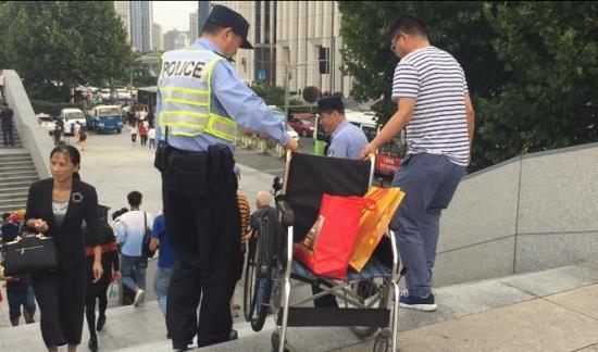 国庆安保巡逻时,陈建国帮助游客搬轮椅。