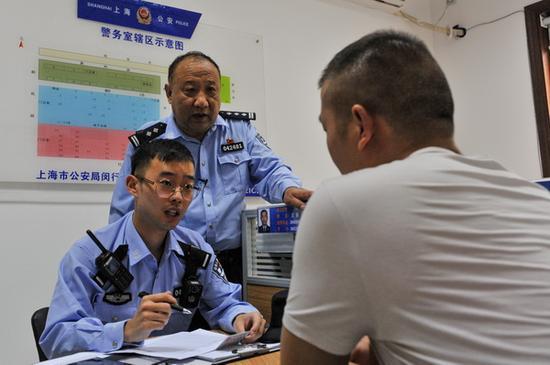 顾侠来指导徒弟蔡文俊登记信息、接受咨询。