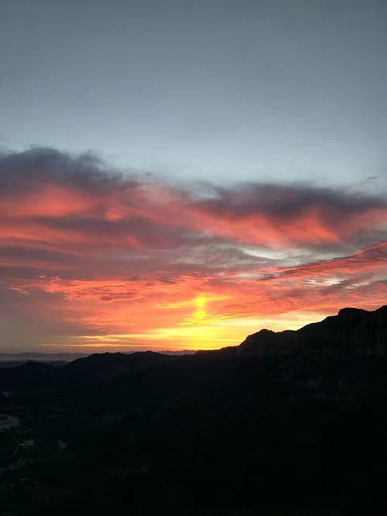 """""""查逃部""""工作人员在山上迎来朝阳。 受访者供图"""