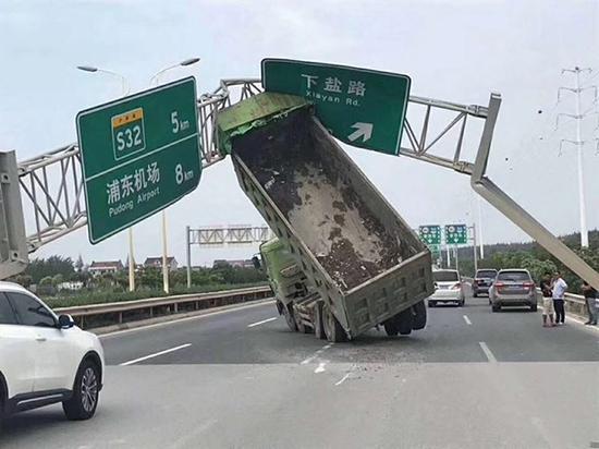 """10月1日11时许,柏某驾驶一辆货车行驶时,升起的车厢将道路上的""""龙门架""""撞坏。 东方网 图"""