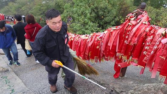 杜小利在华山西峰顶捡游客丢弃的垃圾。
