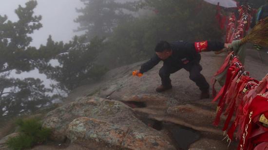 杜小利在华山西峰顶,翻越围栏捡游客丢弃的垃圾。