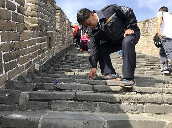 """10月3日,当了33年长城环卫工的王茂海,随时弯腰捡地上的垃圾,他说,这已经是他的""""职业病""""。本文图片 澎湃新闻记者 赵实"""