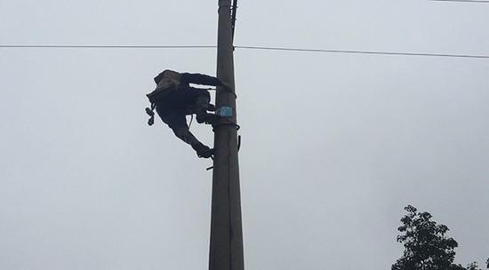 运维工攀爬电杆检查隐患点。