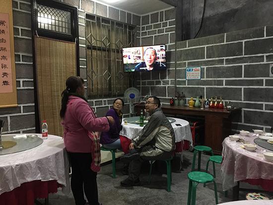 电视里播放介绍郭亮洞的纪录片,王春莲给游客们讲解。