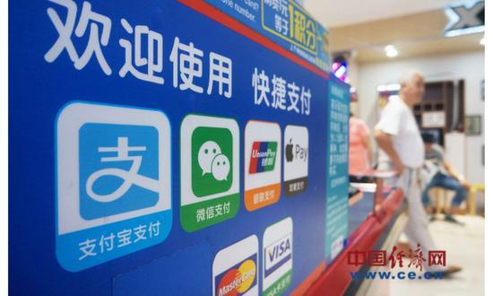 资料图片:2017年9月6日,顾客从杭州一家超市的微信支付、支付宝等非银支付标识前走过。(图片来源:视觉中国)