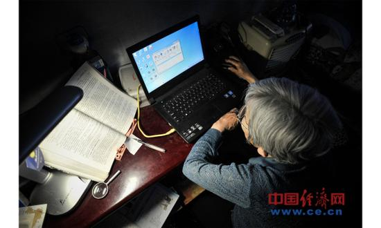 资料图片:2017年5月17日,天津。薛敏修在利用电脑学习。2014年,78岁的薛敏修正式成为天津大学现代远程教育电子商务专业的本科学生。(图片来源:视觉中国)