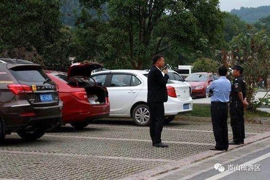 旁边一车尾箱大开,工作人员正在联系车主。