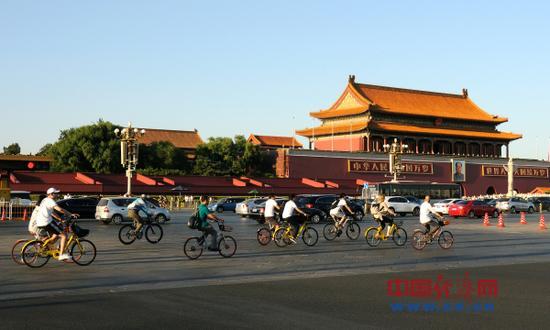 资料图片:2017年9月17日,北京。市民骑共享单车行驶在天安门前及长安街上。(图片来源:视觉中国)