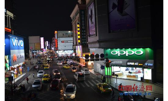 资料图片:2017年2月27日,广东省东莞市塘厦镇手机店铺夜景。(图片来源:视觉中国)