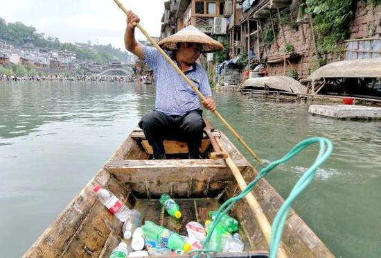 石洪友正在打捞沱江水面的垃圾。