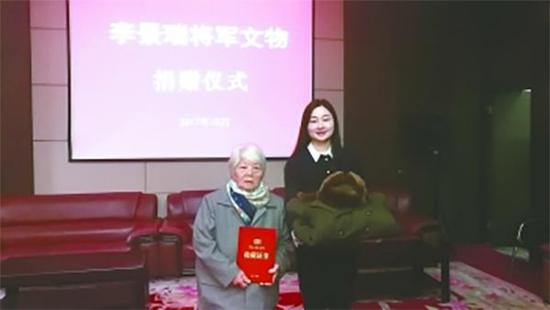 李景瑞夫人徐义宁(左)向新四军纪念馆捐赠将军穿戴过大衣和冬帽。盐城晚报 图