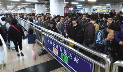 昨日,旅客在北京西站出站后,准备乘地铁离开站区,候乘队伍蜿蜒距离超过300米。图/视觉中国