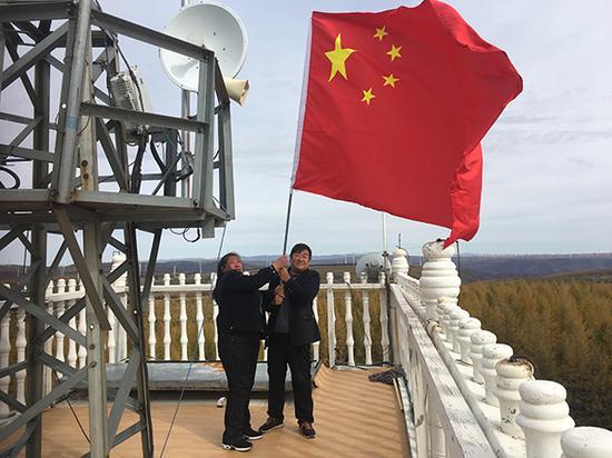 10月1日,刘军、齐淑艳夫妇登上望火楼顶,手持国旗向国庆献礼。本文图片均来自澎湃新闻记者 王哿