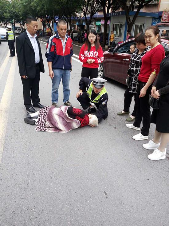 饶晋豪单膝跪地,托住老人头部。 本文图片均为云阳县公安局 供图