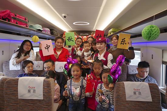 乘务组与乘客合影,共度中秋。视觉中国 图