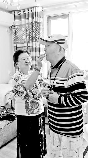 曹雪梅(左)为老伴擦拭嘴角的口水