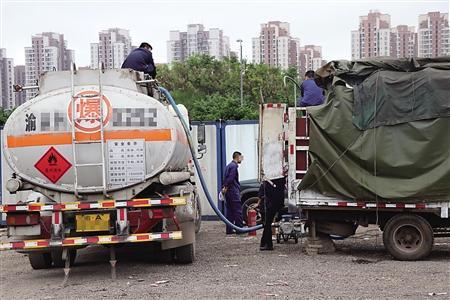油罐车在给白色货车送油