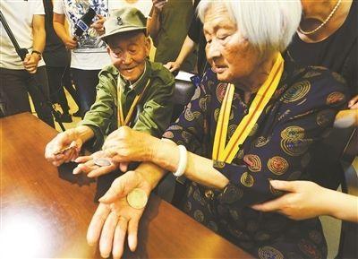 张道干和杨美田向侵华日军南京大屠杀遇难同胞纪念馆捐赠收藏70多年的3块银元和张道干在朱家岗战斗中缴获的一枚日军奖章