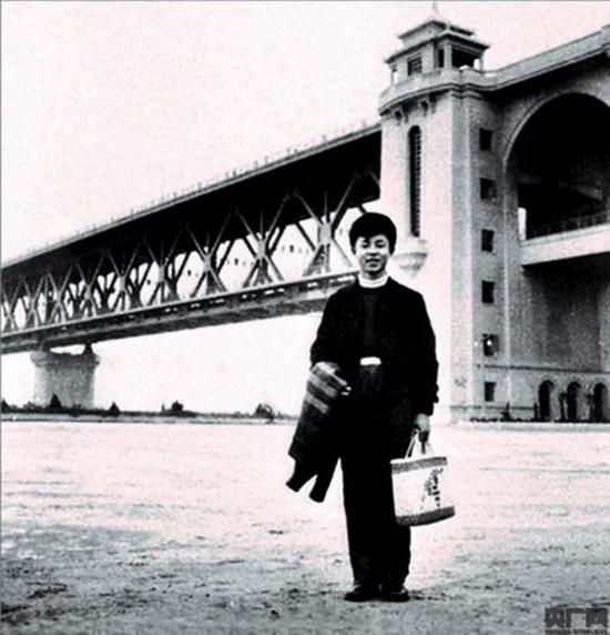"""1958 年11 月初,18岁的雷锋被鞍钢录用,穿着""""时尚""""的雷锋,微笑着站在雄伟的桥头堡下。 /中铁大桥局供图"""