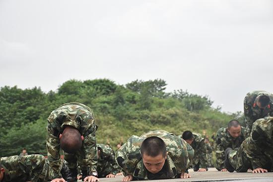体能训练中,很多战友已经支撑不住,但孔文(中)还在不懈坚持,做好每一个俯卧撑