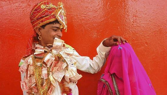 2011年5月,在印度拉治加,14岁的Bablu戴着钞票做的花环准备揭开12岁新娘Mata Bai的盖头。 东方IC 图