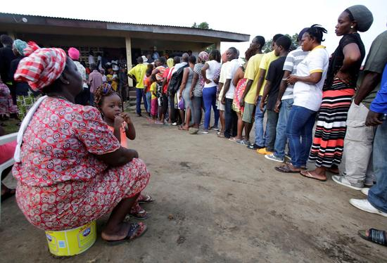 10月10日,在利比里亚首都蒙罗维亚,民众在一处投票点等待投票。 (新华社/路透)