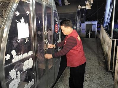 工作人员杨建国最后一次关闭摩天轮轿厢。