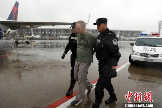 两名特警将美籍红通逃犯押送至机场。 张亨伟 摄