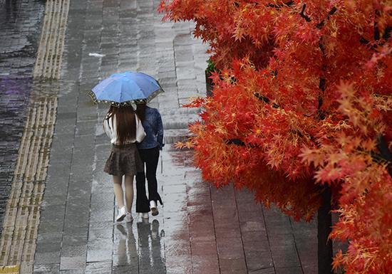 2017年10月11日,西安小寨赛格广场,女孩穿裙装在雨中行走。视觉中国 图