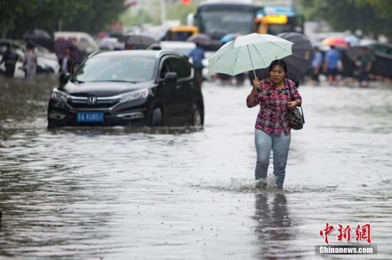 资料图:9月25日,南京城东银城东苑门口的门路上,市民在积水中涉水而行。泱波 摄
