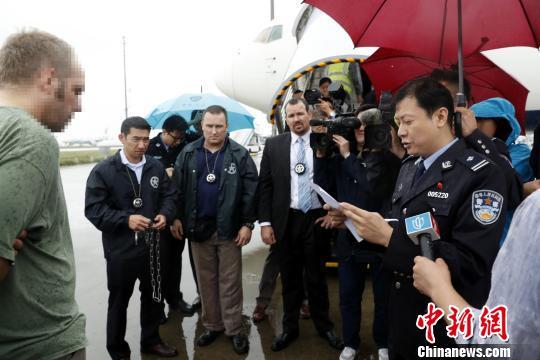中国警方向美籍红通逃犯宣读驱逐出境相关文件。 张亨伟 摄