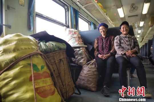 """资料图:""""扶贫""""列车上,妇女正守护着自己的货品。 龚萱 摄"""