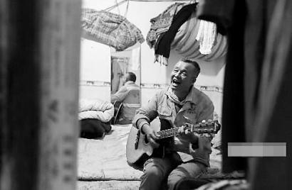 陈大爷在租住的房间里边弹边唱