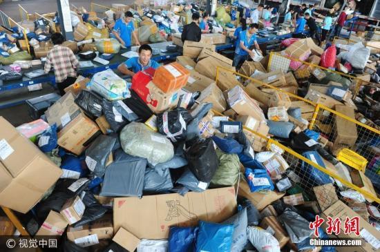 """资料图:位于安徽省阜阳市颍东开发区的某快递公司内,快递工作人员在分拣中心忙碌着分拣""""堆如小山""""的快递包裹。王彪 摄 图片来源:视觉中国"""