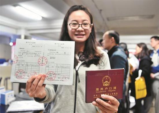 王艳拿到准迁证,兴奋不已。楚天都市报 图