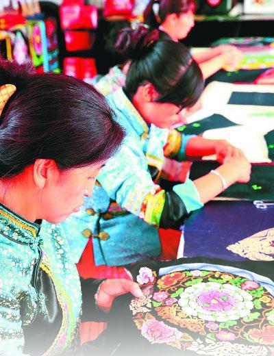 """青海省民和回族土族自治县土族刺绣协会""""妈妈制造""""互助社的土族妇女在制作土族盘绣。"""