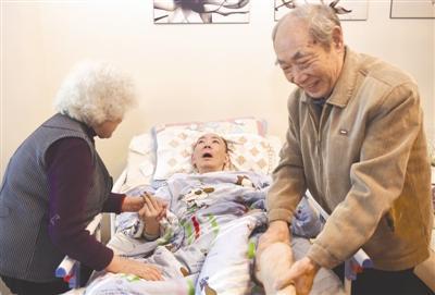 董海清老两口在给瘫痪在床的儿子董月做肢体按摩 摄影记者 张士博