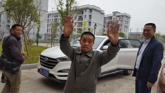 要回家了,姜国良与救助站工作人员挥手告别。受访者供图