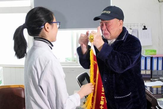 张大爷给兰医生送来锦旗,激动得几次抹眼泪。 四川新闻网 图