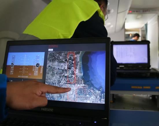 2017年10月14日,在ARJ21-700飞机103架机上,事情职员在展示通过北斗卫星定位系统获得的经纬度实时绘制的飞机航行轨迹图。新华社记者 丁汀 摄
