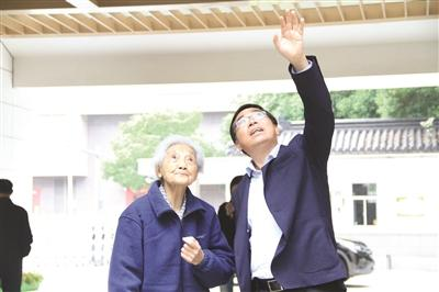李伟平校长陪同周映芳老师(左)参观学校。