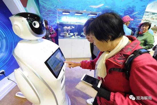 (参观者与低碳知识互动机器人互动)