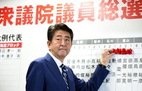 10月22日,在日本东京自民党总部,日本首相、自民党总裁安倍晋三为当选议员贴花。 新华社 图