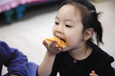 2017年10月18日,一名北京安泰幼儿园之孩子在吃食堂大厨专门为幼儿制造之Pizza。材料图片