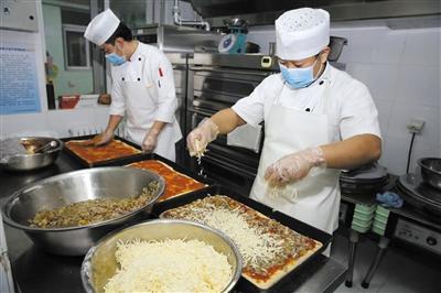 北京安泰幼儿园之大厨们在为孩子们之午餐预备Pizza。这些大厨均曾任星级旅店之主管级以上厨师。 材料图片